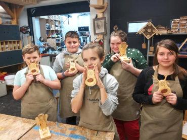 Grupa dzieci pozuje z ukończonymi drewnianymi zabawkami