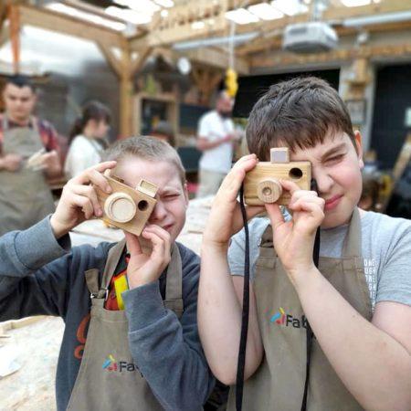 Dzieci pozują z ukończonymi drewnianymi zabawkami