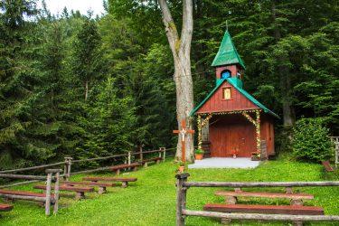 Atrakcje - drewniana kaplica z miejscami do siedzenia na zewnątrz