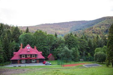 Ośrodek Górski Kordon z zewnątrz, drewniany dom z czerwonym dachem pośrodku lasu