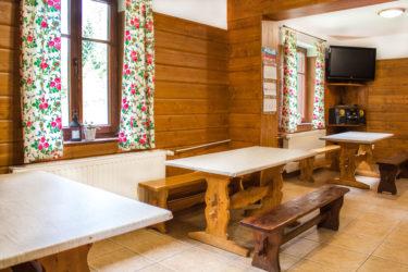 Jadalnia, Ośrodek Górski Kordon, stoły i ławy drewniane oraz telewizor
